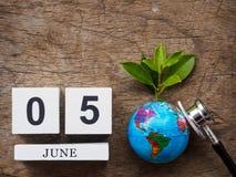 6月05日木日历块、地球和听诊器在木t 免版税库存图片