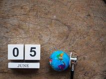 6月05日木日历块、地球和听诊器在木t 图库摄影
