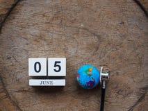 6月05日木日历块、地球和听诊器在木t 库存照片