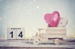 2月14日木葡萄酒日历照片与木玩具卡车的有在黑板前面的心脏的 库存照片