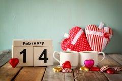 2月14日木葡萄酒日历用在夫妇杯子旁边的五颜六色的心脏形状巧克力在木桌上 选择聚焦 免版税库存照片
