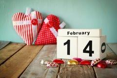 2月14日木葡萄酒日历用在夫妇杯子旁边的五颜六色的心脏形状巧克力在木桌上 选择聚焦 图库摄影