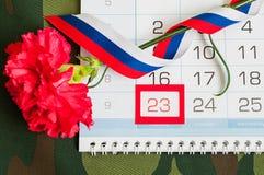 2月23日欢乐卡片 红色康乃馨、俄国旗子和日历与被构筑的日期2月23日在伪装织品 免版税图库摄影