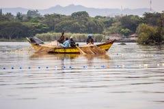 9月2017 17日河马点,基苏木,维多利亚湖,肯尼亚 老木渔的年轻非洲渔夫乘独木舟,带来网 免版税库存图片