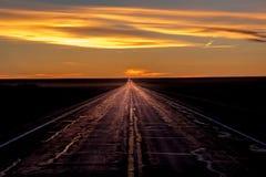 2017年3月8日,内布拉斯加-在农村农厂乡下公路的日落有驾驶由输电线行的卡车的  免版税库存图片