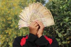 2016年11月9日,印度A未认出的男孩在天空中采取了一些印地安货币 免版税库存照片