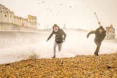 2015年11月29日,布赖顿,英国,海滩的男孩由危险德斯蒙德风暴波浪捉住了 库存图片