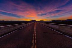 2017年3月12日,拉斯维加斯, NV -在跨境15上的高速公路天桥,在拉斯维加斯南部,日落的内华达与yellowline 免版税库存照片