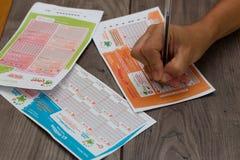 2017年8月2日,黄柏,爱尔兰-接近某人填好一张欧洲数百万票的和爱尔兰人每日百万和乐透纸牌 免版税库存图片
