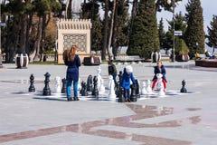2017年3月10日, Azneft广场,巴库,阿塞拜疆 一杆大棋枰在海滨公园,下棋的孩子 图库摄影