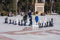 2017年3月10日, Azneft广场,巴库,阿塞拜疆 一杆大棋枰在海滨公园,下棋的孩子 免版税库存图片