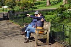 2017年4月16日-伦敦,英国一对未认出的年轻夫妇在公园采取selfie坐一条长凳 免版税库存照片