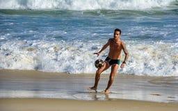 2016年12月6日 供以人员踢在行动的海滩橄榄球在大西洋波浪背景在科帕卡巴纳海滩 库存照片