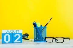 8月2日 图象的威严2,在黄色背景的日历与办公用品 新的成人 免版税库存图片
