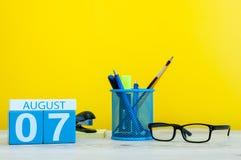 8月7日 图象的威严7,在黄色背景的日历与办公用品 新的成人 免版税库存图片