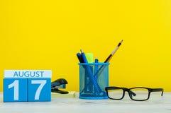 8月17日 图象的威严17,在黄色背景的日历与办公用品 新的成人 免版税库存照片