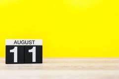 8月11日 图象的威严11,在黄色背景的日历与文本的空的空间 新的成人 图库摄影