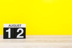 8月12日 图象的威严12,在黄色背景的日历与文本的空的空间 新的成人 免版税库存照片
