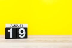 8月19日 图象的威严19,在黄色背景的日历与文本的空的空间 新的成人 免版税库存图片