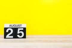 8月25日 图象的威严25,在黄色背景的日历与文本的空的空间 新的成人 库存照片