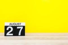 8月27日 图象的威严27,在黄色背景的日历与文本的空的空间 新的成人 库存图片