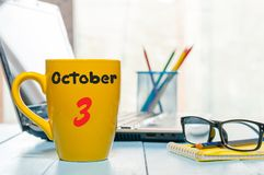 10月3日 在早晨黄色杯子的天3月,日历用咖啡或茶,学生工作场所背景 秋天 库存照片