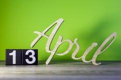 4月13日 在木桌上的天13月,日历和绿色背景 春天,文本的空的空间 库存图片