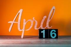 4月16日 在木桌上的天16月,日历和绿色背景 春天,文本的空的空间 库存图片