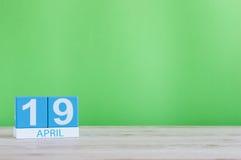 4月19日 在木桌上的天19月,日历和绿色背景 春天,文本的空的空间 免版税库存照片