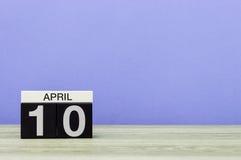4月10日 在木桌上的天10月,日历和紫色背景 春天,文本的空的空间 免版税库存图片