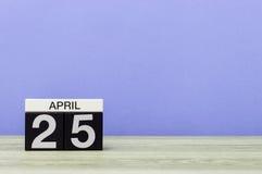 4月25日 在木桌上的天25月,日历和紫色背景 春天,文本的空的空间 库存图片