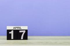4月17日 在木桌上的天17月,日历和紫色背景 春天,文本的空的空间 免版税库存照片