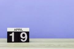 4月19日 在木桌上的天19月,日历和紫色背景 春天,文本的空的空间 库存图片