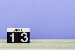 4月13日 在木桌上的天13月,日历和紫色背景 春天,文本的空的空间 免版税库存照片