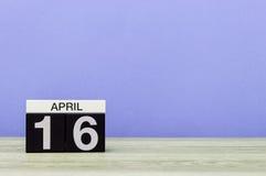 4月16日 在木桌上的天16月,日历和紫色背景 春天,文本的空的空间 免版税库存图片