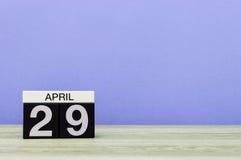 4月29日 在木桌上的天29月,日历和紫色背景 春天,文本的空的空间 库存图片