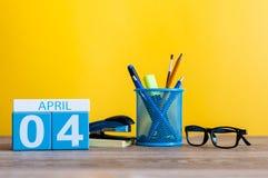 4月4日 在桌上的天4 4月月,日历有黄色背景和办公室或者学校用品 春天…上升了叶子,自然本底 免版税库存照片