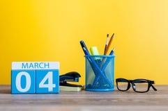 3月4日 在桌上的天4行军月,日历有黄色背景和办公室或者学校用品 春天…上升了叶子,自然本底 库存图片