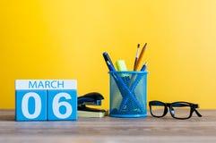 3月6日 在桌上的天6行军月,日历有黄色背景和办公室或者学校用品 春天…上升了叶子,自然本底 库存照片
