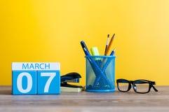 3月7日 在桌上的天7行军月,日历有黄色背景和办公室或者学校用品 春天…上升了叶子,自然本底 库存照片