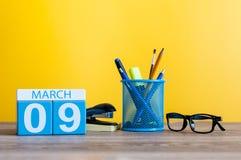 3月9日 在桌上的天9行军月,日历有黄色背景和办公室或者学校用品 春天…上升了叶子,自然本底 图库摄影