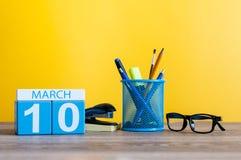 3月10日 在桌上的天10行军月,日历有黄色背景和办公室或者学校用品 春天…上升了叶子,自然本底 免版税库存图片