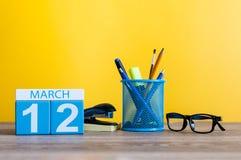 3月12日 在桌上的天12行军月,日历有黄色背景和办公室或者学校用品 春天…上升了叶子,自然本底 免版税库存图片