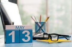 5月13日 在营业所背景的天13月,有膝上型计算机的日历,工作场所和玻璃 春天,空 库存照片