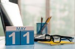 5月11日 在营业所背景的天11月,有膝上型计算机的日历,工作场所和玻璃 春天,空 免版税图库摄影
