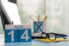 5月14日 在营业所背景的天14月,有膝上型计算机的日历,工作场所和玻璃 春天,空 免版税库存图片