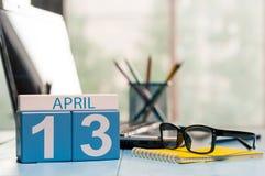 4月13日 在营业所背景的天13月,有膝上型计算机的日历,工作场所和玻璃 春天…上升了叶子,自然本底 库存照片