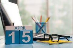 4月15日 在营业所背景的天15月,有膝上型计算机的日历,工作场所和玻璃 春天…上升了叶子,自然本底 免版税库存照片