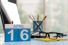 4月16日 在营业所背景的天16月,有膝上型计算机的日历,工作场所和玻璃 春天…上升了叶子,自然本底 库存照片