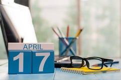 4月17日 在营业所背景的天17月,有膝上型计算机的日历,工作场所和玻璃 春天…上升了叶子,自然本底 免版税库存照片